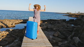 Happy young woman on vacation with a suitcase. Travel concept stock footage