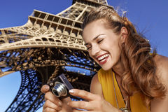 Happy young woman viewing photos in front of Eiffel tower Royalty Free Stock Images