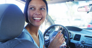 Happy young woman waiting in her car Stock Images