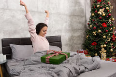 Happy young woman wake up and rejoice at her christmas present w Stock Image
