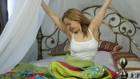 Happy, young woman wakes up and dancing on bed at home. slow motion stock footage