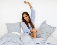 Happy young woman waking up in bed Stock Photo