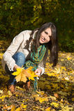 Happy young woman on a walk in autumn holding leaves in her hand Royalty Free Stock Photos