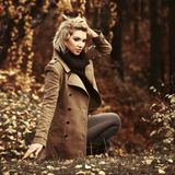 Happy young blond fashion woman walking in autumn city park royalty free stock photo