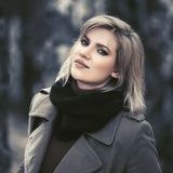 Happy young blond fashion woman walking in autumn park stock photography