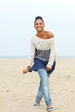 Happy young woman walking on beach in jeans and sweater Royalty Free Stock Photos