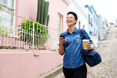 Happy young woman walking with cellphone and bag Royalty Free Stock Photos