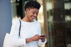 Happy young woman walking in the city sending text message Royalty Free Stock Image