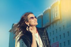 Happy young woman walking on a city street. royalty free stock images