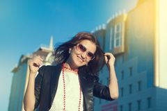 Happy young woman walking on a city street. stock images