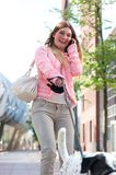 Happy young woman walking her dog in the city and talking on the phone Stock Photography