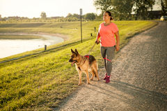 Happy young woman walking  with her German Shepherd Dog Stock Images