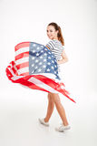 Happy young woman walking and holding usa flag Stock Photos