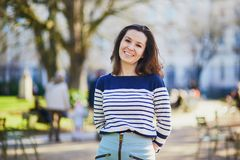 Happy young woman walking in the Luxembourg garden of Paris. France on a sunny spring day royalty free stock image