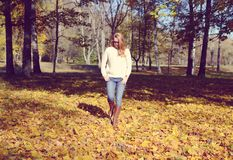 Happy young woman walking in park. On sunny autumn day Royalty Free Stock Photos