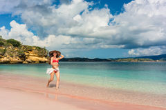Happy young woman walking through shallow sea water on the beach Stock Image