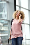 Happy young woman walking with suitcase and mobile phone Royalty Free Stock Images