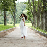 Happy young woman walking on the summer park Royalty Free Stock Photography