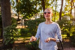 Happy young woman walking in summer park. Girl wearing stylish clothes and accessories stock images