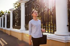 Happy young woman walking in summer park. College student smiling outdoors royalty free stock photos