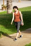 Happy young woman walking to yoga lesson in park. Full length portrait of happy young woman walking to yoga lesson in park Stock Photo
