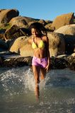 Happy young woman walking in water at the beach Stock Image