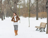 Happy young woman walking in winter park Royalty Free Stock Photography