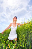 Happy young woman is walking in a yellow field Royalty Free Stock Photos