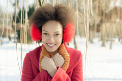 Happy young woman with warm on ears enjoying winter sunshine Stock Photography