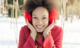 Happy young woman with warm on ears enjoying winter sunshine Stock Images