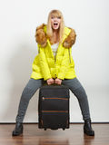 Happy young woman in warm jacket with suitcase. Stock Photo