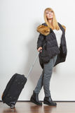 Happy young woman in warm jacket with suitcase. Stock Images