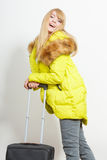 Happy young woman in warm jacket with suitcase. Stock Photos