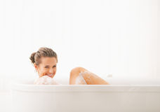 Happy young woman washing in bathtub Stock Photos