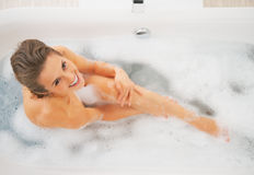 Happy young woman washing in bathtub Royalty Free Stock Photography