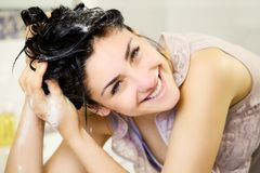 Happy young woman washing black hair smiling Royalty Free Stock Photos