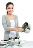 Washing dishes. Happy Young Woman Washing Dishes in the kitchen Stock Photography