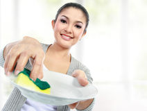 Washing dishes. Happy Young Woman Washing Dishes in the kitchen Royalty Free Stock Images