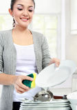Washing dishes. Happy Young Woman Washing Dishes in the kitchen Stock Image