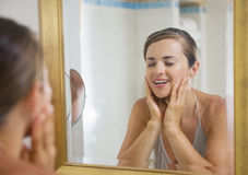 Happy young woman washing face in bathroom Stock Image