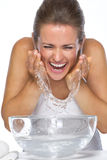 Happy young woman washing face in glass bowl with water. Isolated on white Stock Photography
