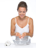 Happy young woman washing hands in glass bowl with water Royalty Free Stock Photo