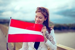 Happy young woman watching and holding Austrian flag stock photos