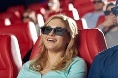 Happy young woman watching movie in theater. Cinema, entertainment, technology and people concept - happy young women in 3d glasses watching comedy and laughing Royalty Free Stock Image