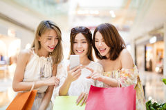 Happy young woman  watching smart phone in shopping mall. Happy young women group watching smart phone in shopping mall Royalty Free Stock Images
