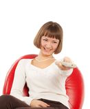 Happy young woman watching TV. Happy young woman pointing remote control at TV Royalty Free Stock Photography