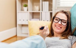 Happy young woman watching TV. In the living room Royalty Free Stock Photos
