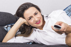 Happy young woman watching tv Stock Photos