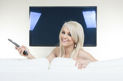 Happy young woman watching tv on sofa Stock Image