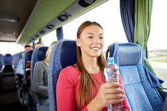 Happy young woman with water bottle in travel bus Stock Photography